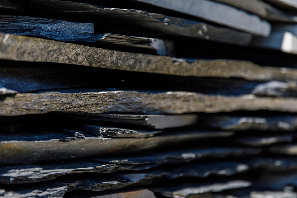 Schwarze Schieferplatten aufgestapelt, bei Projekt Garten.